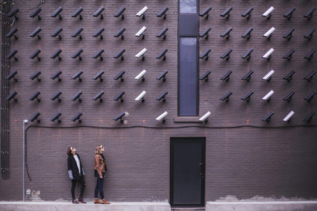 Ściana pełna kamer które są skierowane na dwie osoby