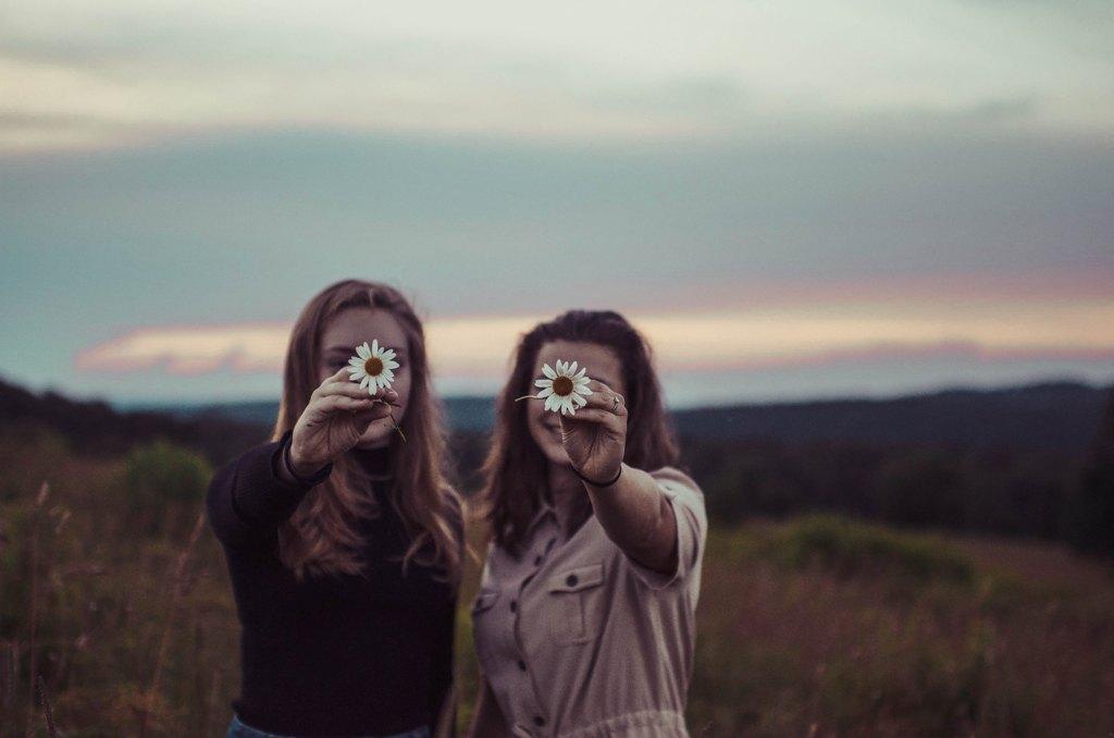 Dwie młode kobiety z kwiatkiem w dłoni