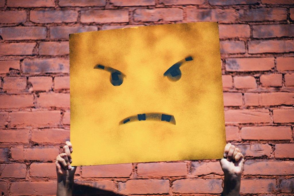 Złowrogi krytykujący wyraz twarzy na tle muru